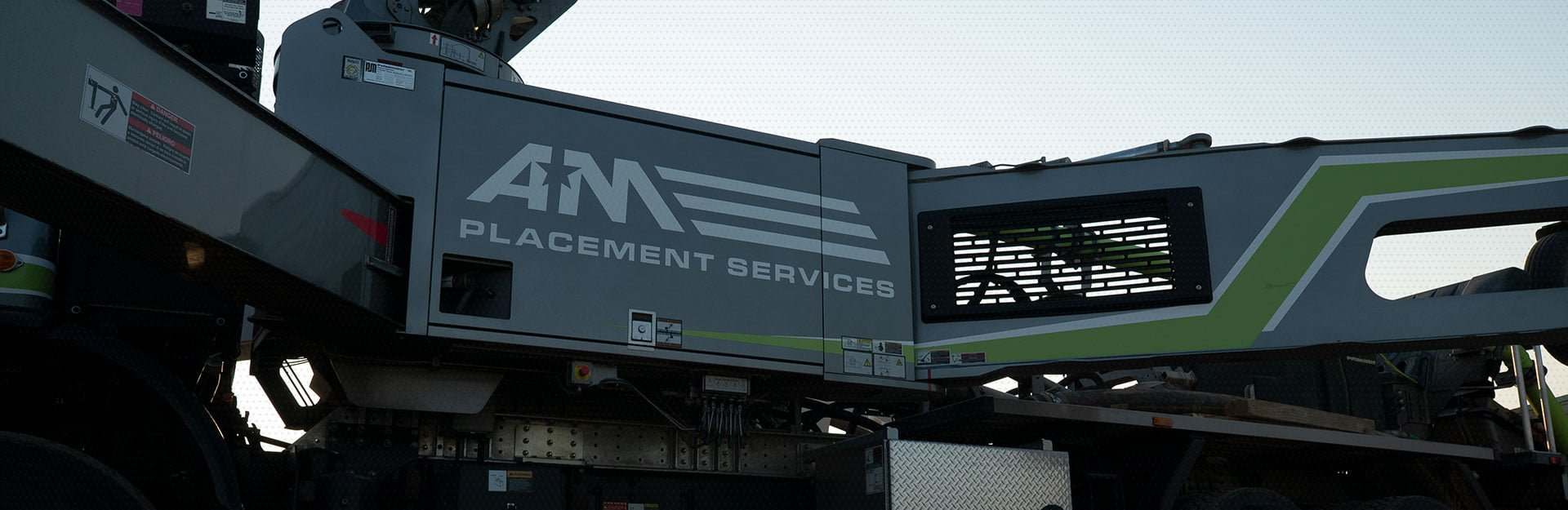 An AM Placement Services machinery that is a dark-green color with the AM logo being featured on the side of the machine.