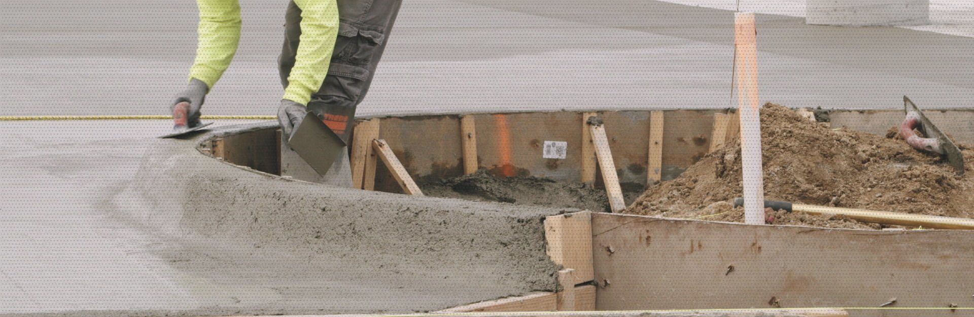 AM Contracting employees maneuvering wet cement from the surface into an upwards angle creating a sidewalk curb